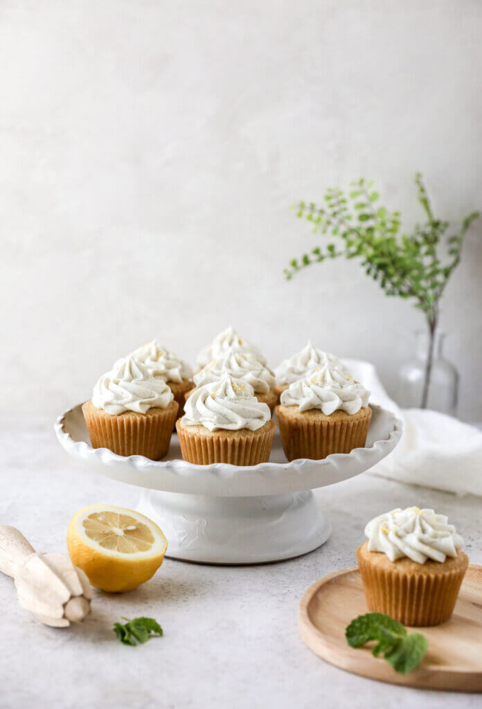 A cake stand with gluten-free lemon cupcakes with another side plate with a lemon cupcake and a sprig of mint.