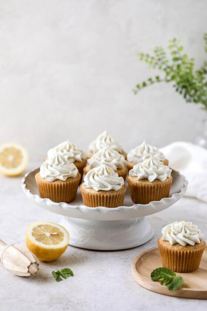 A cake stand with frosted cupcakes and lemons scattered around and one plate with a cupcake on it.