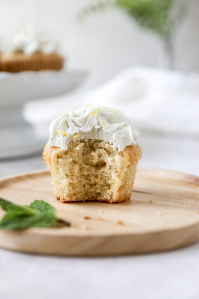 Straight on view of a lemon cupcake with a bite taken out of it.