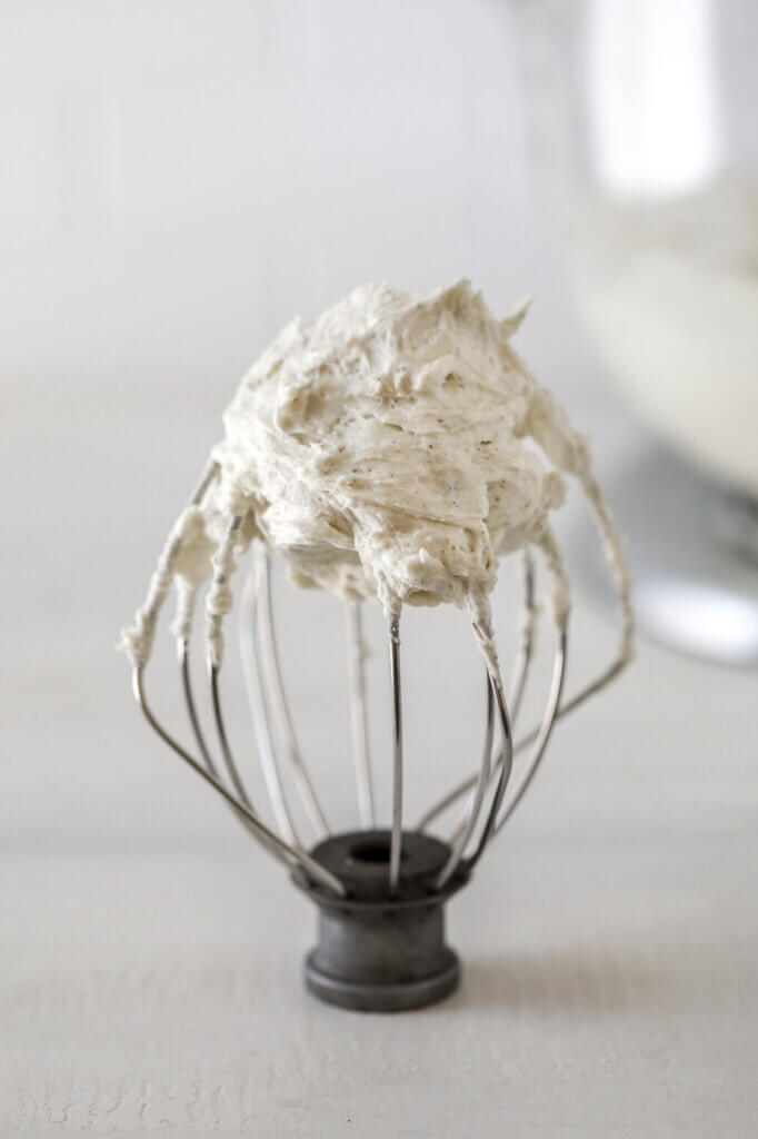 A mixer whisk attachment with dairy-free buttercream.